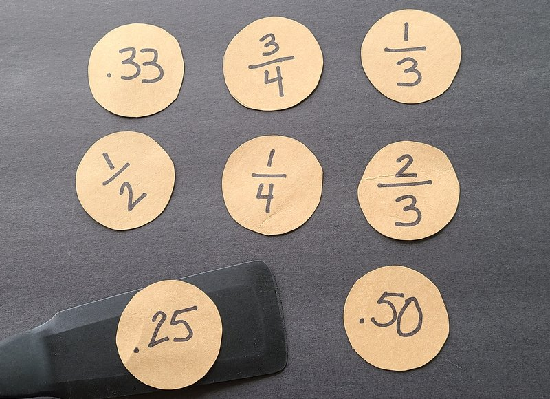 Fraction and decimal flashcards made of cardboard circles, with a spatula flipping one