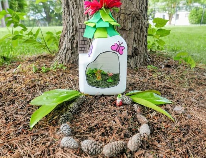 Fairy house made from a plastic gallon milk jug in a garden with pinecones (Reuse Materials For Art)