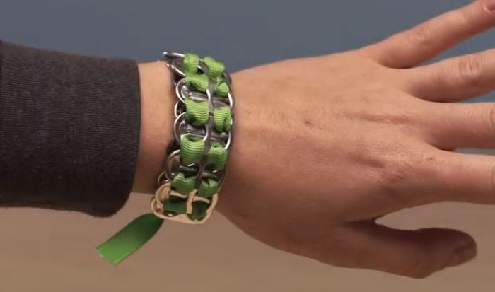 Bracelet made from pop tops and green ribbon on a woman's wrist