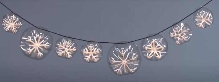 Snowflake garland made from the bottoms of plastic bottles and white paint (Reuse Materials For Art)